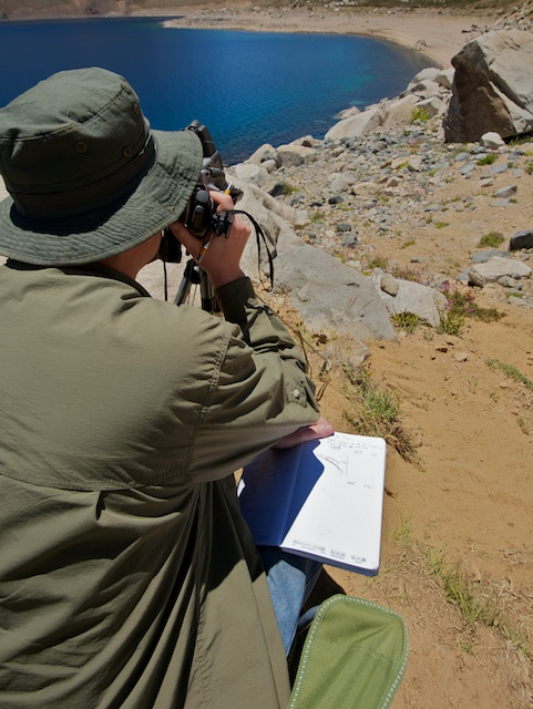 Jeff Moersch squints at the heat maps of the Laguna Negra terrain produced by his thermal imager, carefully jotting down in his field notebook information about where the imager is pointed. Credit: Henry Bortman