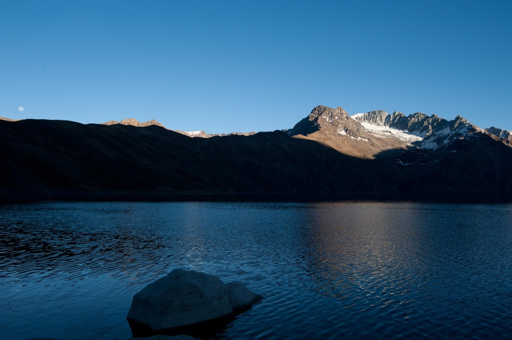 As the nearly full moon sets in the west, early light on Cerro Echaurren is reflected on the still water of Laguna Negra.
