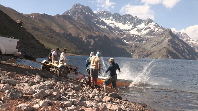 The pontoon that will eventually form the floating base of the Planetary Lake Lander robot splashes down into the waters of Laguna Negra. Left to right: Trey Smith, Chris Haberle, Liam Pedersen, Cristian Tambley, Gavin Saville, Geoff Saville. Credit: XenoQuest Media